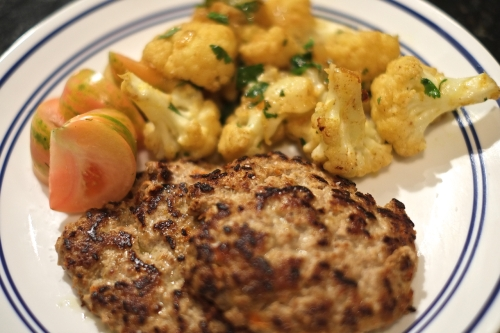 Veal burgers with curried cauliflower and tomatoes
